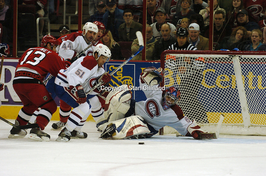 Montreal Canadiens' goaltender Jose Theodore eyes the puck along with defenseman Francis Bouillon (51) and Sheldon Souray (44) as the Carolina Hurricanes' Ray Whitney (13) sneaks in during their game Saturday, Dec. 31, 2005 in Raleigh, NC. Carolina won 5-3.