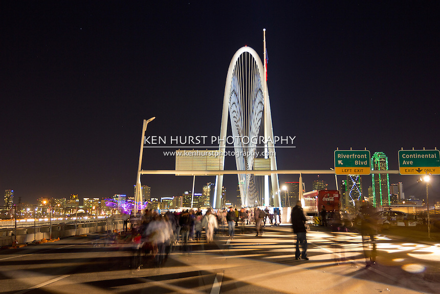 Crowds of people walking on the bridge at the opening celebration for the newly constructed (2012) Margaret Hunt Hill bridge, designed by Santiago Calatrava, with the night lights of Dallas, Texas in the background.