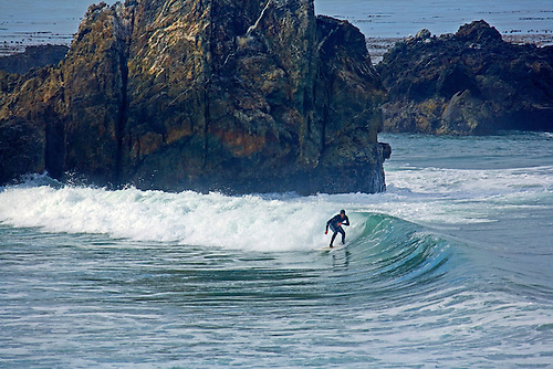 SURFER NEGOTIATING WAVES AND ROCKS ON THE BIG SUR COAST ALONG PACIFIC OCEAN, CALIFORNIA
