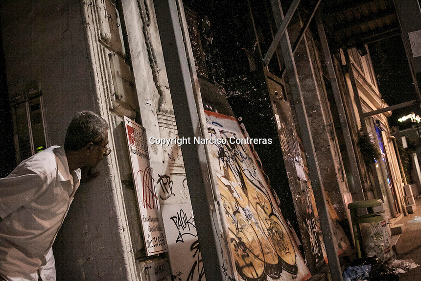 In this Saturday, Jun. 15, 2013 photo, a resident watchs the clashes over Istiklal street after anti-riot police attacked a peaceful rally in Gezi park of Taksim Square during the ongoing turmoil in Istanbul, Turkey. (Photo/Narciso Contreras).