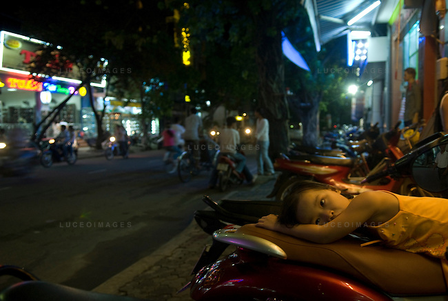 A Vietnamese girl relaxes on the back of her mother's motor bike outside of a restaurant in Ho Chi Minh City, Vietnam.