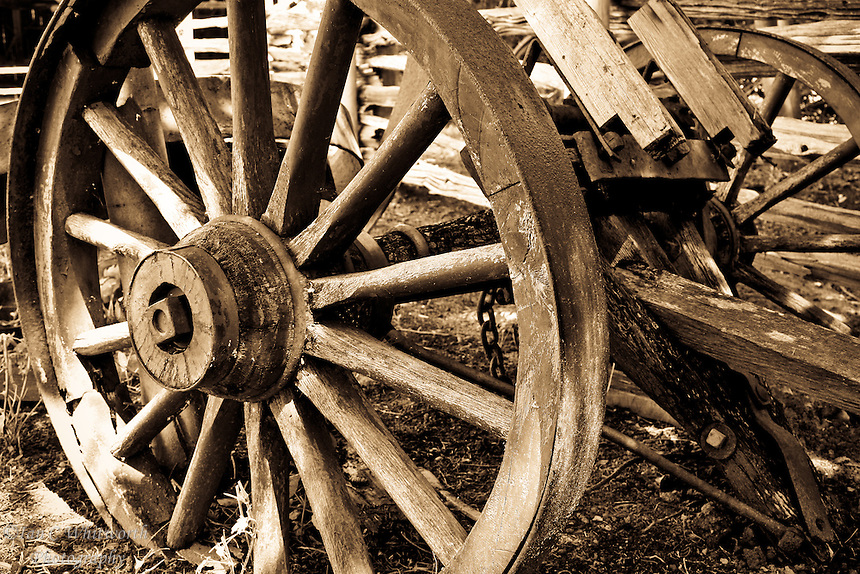 Abandoned old wooden wagon wheels and axle in B&W