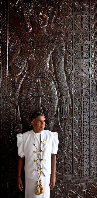 """A doorman watches the entrance in front of huge wood carved doors at The Galle Face Hotel. Founded in Colombo, Sri Lanka in 1864, is the oldest hotel east of Suez. It is located off Galle Road, the main highway in the City of Colombo.The hotel borrowed its name from this charming way back of """"Galle Face Green"""" in 1864, built by four British entrepreneurs who were looking to start a business in the city..Mignonne Fernando and The Jetliners regularly entertained guests at the Coconut Grove, the night club attached to the hotel. The venue was even popularised in a song. Radio Ceylon recorded music programmes from the Coconut Grove as well as the Galle Face Hotel itself, presented by some of the legendary Radio Ceylon announcers in the 1950s and 1960s, such as Livy Wijemanne and Vernon Corea. Thousands listened to the broadcasts, particularly 'New Year's Eve' dances from the Galle Face Hotel..D.G. William (known as 'Galle Face William'), the Lanka Sama Samaja Party trade union leader, first worked and organised workers here. The Science fiction author Arthur C. Clarke wrote the final chapters of 3001 - The Final Odyssey in the hotel..It regularly featured on the itineraries of royalty . Princess Alexandra of Denmark commented that 'the peacefulness and generosity encountered at the Galle Face Hotel cannot be matched'. Former guests include the first man in space, Yuri Gagarin, former British Prime minister Edward Heath, the journalist Eric Ellis and Prince Sadruddhin Aga Khan, Rigger Bone Sconi, Lord Louis Mountbatten, 1st Earl Mountbatten of Burma and Marshal Josip Broz Tito."""
