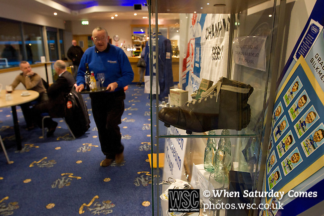 Macclesfield Town 0 Gateshead 4, 22/02/2013. Moss Rose, Football Conference. A man carrying a tray of beer past an historical display in the hospitality suite before Macclesfield Town host Gateshead at Moss Rose in a Conference National fixture. The visitors from the North East who were in the relegation zone, shocked Macclesfield with four first half goals and won 4-0 in front of 1467 fans. Both teams were former members of the Football league, with Macclesfield dropping out in 2012. Photo by Colin McPherson.