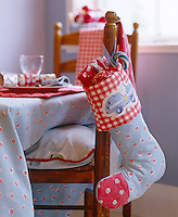 Detail of a Christmas stocking filled with treats hanging on the back of a chair