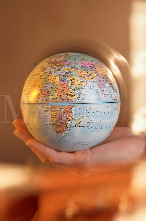 Blurred motion image of a hand holding a globe.