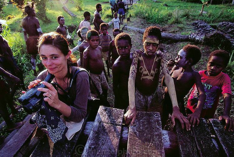 On Good Friday in the Asmattan village of Komor, Faith D'Aluisio stands with a group of village youths in Komor village, Asmat swamp, Irian Jaya, Indonesia. (Man Eating Bugs page 187)