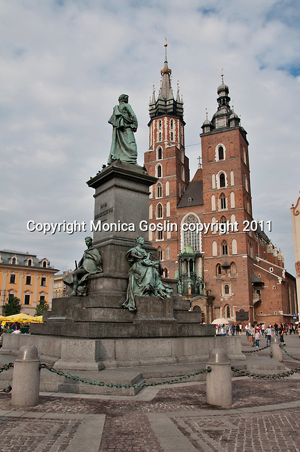 The Adam Mickiewicz Monument in Krakow, Poland on the Maint Market Square and in front of St. Mary's Church. The Monument is dedicated to the 19th century poet, Adam Mickiewicz, his statue is on top of the monument and surrounded by four allegoric groups: Sicence, Courage, Poetry, and Motherland
