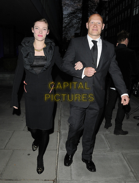 CAMILLA RUTHERFORD & DOMINIC BURNS.'An Evening at the Sanderson' celebrating 10 years, at the Sanderson Hotel, London, England. .April 27th 2010.full length black dress long sleeves ruffle collar couple tights suit arms linked.CAP/CAN.©Can Nguyen/Capital Pictures.