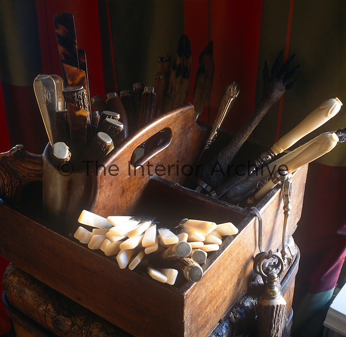 Antique cutlery with bone and silver handles are arranged in a wooden box with a handle.