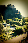 Edinburgh Castle and gardens with summer sunlight and people relaxing in public gardens
