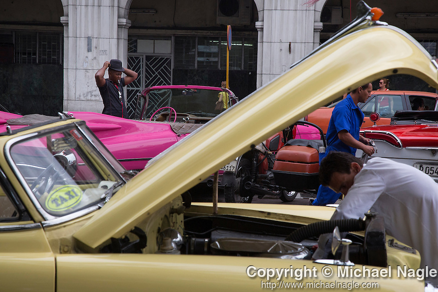 HAVANA, CUBA -- MARCH 24, 2015:   Classic American car drivers wait for tourists in front of the National Capitol Building in Havana, Cuba on March 24, 2015. Photograph by Michael Nagle