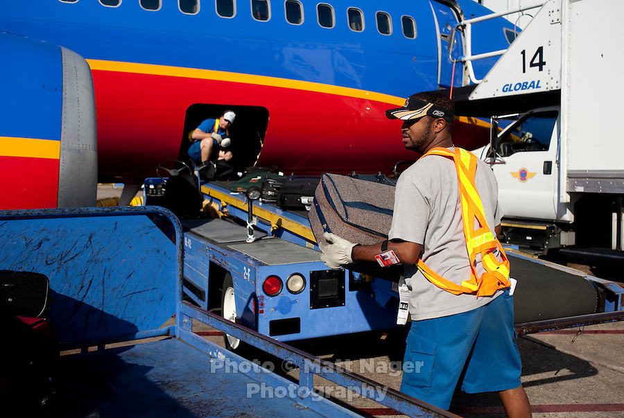 "Southwest Airlines employee Fabian Cordova (cq) moves bags off a plane at Love Field Airport in Dallas, Texas, Wednesday, October 27, 2010. A big selling point for Southwest Airlines has been their ""Bags Fly Free"" campaign...PHOTO/ MATT NAGER"
