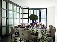 A glamorous dining room with armchair dining chairs upholstered in a linen from Nicholas Haslam Ltd. The tablecloth was a gift from fashion designer Tory Burch. Wood-and-frosted-glass sliding doors lead to the kitchen.