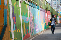 A man looks at his smart phone as he walks in the street next to the painted embankment of a railway line near Okubo,  Shinjuku, Tokyo, Japan. Friday June 17th 2016