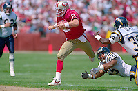 SAN FRANCISCO, CA - Quarterback Steve Young of the San Francisco 49ers runs with the football during a game against the San Diego Chargers at Candlestick Park in San Francisco, California in 1991. Photo by Brad Mangin