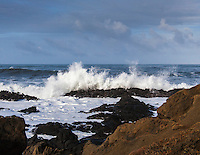 The Pacific Ocean draws the horizon in the distance with clouds above and white, crashing waves and rocky shore close at hand.  Bean Hollow State Beach.