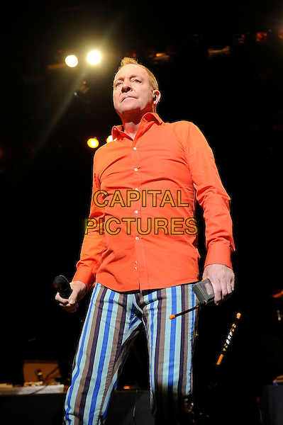 Fred Schneider<br /> The B 52's performing in concert, Indigo2, Greenwich, London, England. 16th August 2013<br /> on stage in concert live gig performance performing music half length orange shirt blue white stripe trousers    <br /> CAP/MAR<br /> &copy; Martin Harris/Capital Pictures