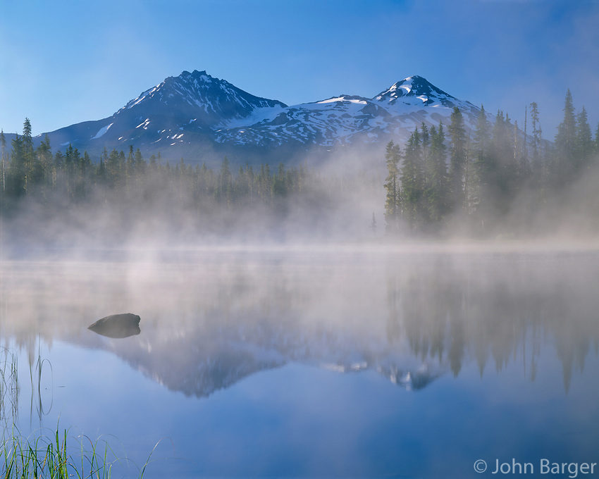 ORCAC_116 - USA, Oregon, Willamette National Forest, North (left) and Middle Sister (right) reflect in Scott Lake while early morning fog swirls above the lake.