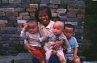 A GRAND-MOTHER PROUDLY DISPLAYS HER THREE MALE GRAN-CHILDREN IN A SMALL VILLAGE IN FOGUANG COUNTY GUANGDON, CHINA.  THE POLICY HAS RESULTED IN MANY MORE BOYS THAN GIRLS BEING BORN AND AN IMBALANCE IN THE POPULATION.