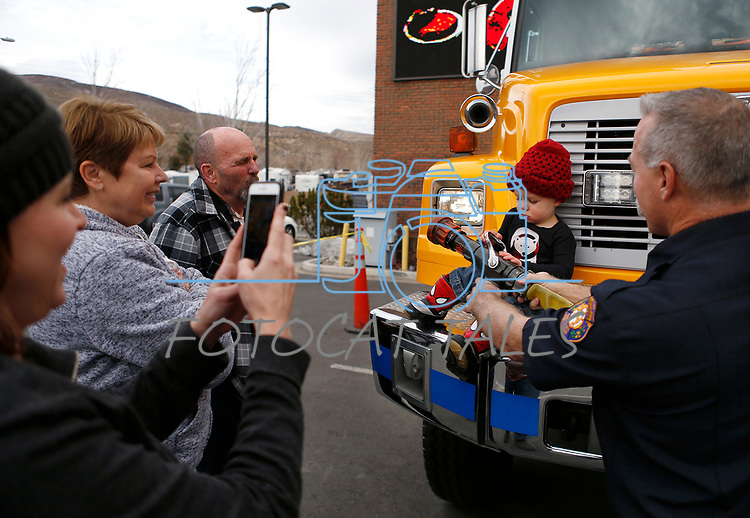 The Jack family takes photos on the fire truck as first responders from around the area wait on diners at Bodines as part of the Feast with a Hero fundraiser in Carson City, Nev., on Saturday, Dec. 15, 2018. <br /> Photo by Cathleen Allison/Nevada Momentum