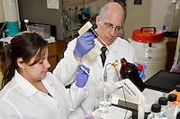 Dr. Luana Torres (DVM), assists Dr. Cody Coyne in lab.