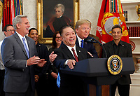 United States President Donald J. Trump hugs Broadcom CEO Hock Tan as Tan announces that Broadcom Limited, a semiconductor manufacturing company, is moving its headquarters from Singapore to the US in the Oval Office of the White House in Washington, DC on Thursday, November 2, 2017.  Broadcom Limited is a Fortune 100 company that currently employs over 7,500 workers in many states across the US.  At left is US House Majority Leader Kevin McCarthy (Republican of California).<br /> Credit: Martin H. Simon / Pool via CNP /MediaPunch