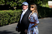 United States President Donald J. Trump calls out to a question from the press pool as he and first lady Melania Trump hold hands as they cross the South Lawn upon arrival at the White House on July 8, 2018 in Washington, DC. The First Family spent the weekend at the Trump National Golf Club in Bedminster Township, New Jersey.<br /> CAP/MPI/RS<br /> &copy;RS/MPI/Capital Pictures