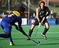 Malaysia's Muhammad Amin Rahim passes across Hayden Shaw during the international hockey match between the New Zealand Black Sticks and Malaysia at Fitzherbert Park, Palmerston North, New Zealand on Sunday, 9 August 2009. Photo: Dave Lintott / lintottphoto.co.nz
