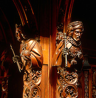 A pair of carved wooden figures that decorate the pillars flanking the doorway, which leads from the Press Gallery in the Lord's Chamber