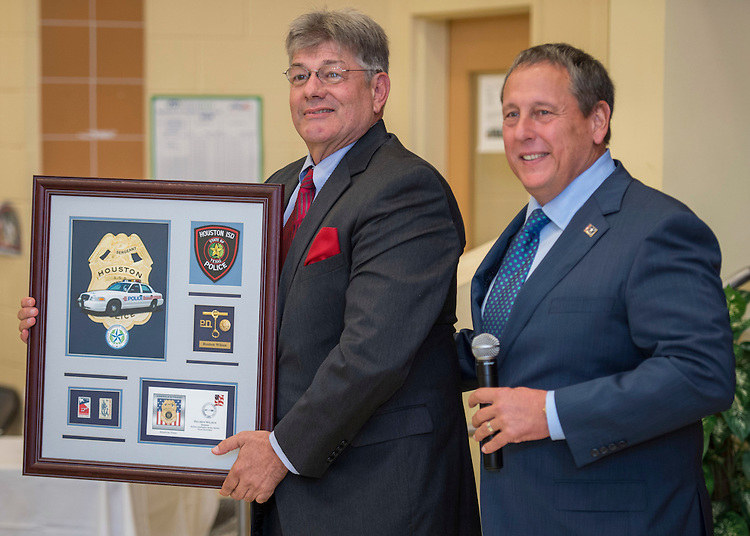 Chief Robert Mock, right, honors retired officer Reuben Wilson, left, during the Houston ISD Police awards banquet at Thompson Elementary School, August 15, 2014.