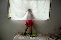 A Waorani (Huaroni) girl, standing behind a curtain, looks out of a window.