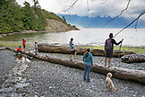 CANADA, Vancouver, British Columbia, family and friends walk on drift logs at Brigade Bay on Gambier Island, in the Howe Sound with the Britannia Range in the distance