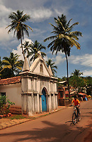A boy rides his bicycle along a narrow road outside a chapel in the hot afternoon in a Goan village in India