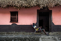 An old Colombian man sits in a rocking chair in front of his house in San Basilio de Palenque, a village in the Caribbean region of Colombia, 14 December 2017.