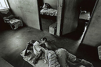 UPINGTON, SOUTH AFRICA - FEBRUARY 8: Two people rest on the floor of a house February 8, 2002 in Loisevale near Upington, South Africa. The house is the location where Baby Thsepang, an 8-month-old baby, was raped by her father in October 2001. Loisevale is a poor and destitute colored/black township where unemployment is high, and a number of social problems including domestic violence and alcohol abuse. The baby rape shocked the country, and it is struggling with an increasing number of rapes and sexual abuse of young children. The country has the highest number of rapes in the world. (Photo by Per-Anders Pettersson)