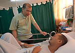 The Rev. Victor Layug, a United Methodist chaplain in the Mary Johnston Hospital in Manila, Philippines, visits with patient Norman Sy.<br /> <br /> The hospital is supported by United Methodist Women.