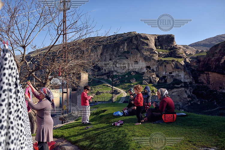 A woman hangs out washing to dry while others rest nearby Hasankeyf. 80% of the town will be submerged beneath 60 metres (200 feet) of water following the completion of the Ilisu hydroelectric dam, 96 kilometres (60 miles) downstream on the Tigris River. The reservoir created by the dam will be approximately of 313 km2 (121 sq mi) and will flood several villages as well as Hasankeyf.