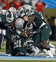 Ohio State Buckeyes running back Carlos Hyde (34) gets stopped by the Michigan State Spartans defense in the 3rd quarter during the Big 10 Championship game at Lucas Oil Stadium in Indianapolis, Ind on December 7, 2013.  (Dispatch photo by Kyle Robertson)