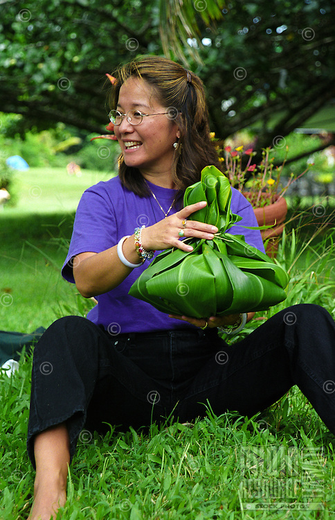 Woman at Kalani Honua retreat center making a Hawaiian hookupu offering out of ti leaves, Big Island