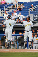 West Virginia Black Bears Kevin Mahala (5) high fives Sandy Santos (27) after hitting a home run during a game against the Batavia Muckdogs on August 21, 2016 at Dwyer Stadium in Batavia, New York.  West Virginia defeated Batavia 6-5.  (Mike Janes/Four Seam Images)