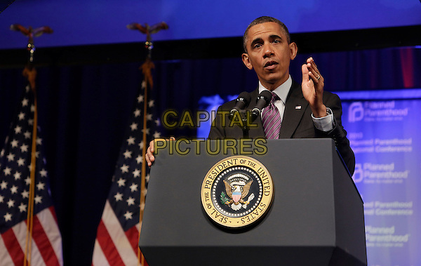 Barack Obama.United States President Barack Obama speaking at the Planned Parenthood Gala at the Washington Marriott Wardman Park Hotel in Washington, DC, USA, April 26, 2013..half length suit tie speaking podium purple american flags politics hand microphone .CAP/ADM/CNP/CK.©Chris Kleponis/AdMedia/Capital Pictures