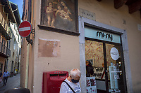 Italy. Lombardy Region. Como. Town center. An elderly man wears in the streets a mask against Coronavirus ( also called Covid-19). A shops sells make up accessories for women. On the wall, a religious painting about the Virgin Mary holding her son jesus Christ in her arms. A red letter box from the Italian Post service. A no-entry traffic sign. Como is a city and comune. It is the administrative capital of the Province of Como. 8.07.2020  © 2020 Didier Ruef
