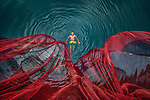 """A young man swims next to huge fishing nets hung out to dry in the sun to keep them clean from alage and sludge build up.<br /> <br /> The man in his early 20s was swimming past the nets hung from a bridge in a canal in Sahjahanpur Upazila, Bangladesh.<br /> <br /> Photographer, Abdul Momin, 29, said """"These are huge fishing nets. Local fishermen of the area sew multiple nets together to make a huge one.  The nets are hung from a bridge which crossed the Canal. After fishing, fishermen wash and hang their nets to dry in sunlight so that mud doesn't damage the net.""""<br /> <br /> Please byline: Abdul Momin/Solent News<br /> <br /> © Abdul Momin/Solent News & Photo Agency<br /> UK +44 (0) 2380 458800"""