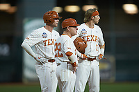 Duke Ellis (11) of the Texas Longhorns stands at third base with teammate Austin Todd (44) and head coach David Pierce (22) during a pitching change during the game against the Missouri Tigers in game eight of the 2020 Shriners Hospitals for Children College Classic at Minute Maid Park on March 1, 2020 in Houston, Texas. The Tigers defeated the Longhorns 9-8. (Brian Westerholt/Four Seam Images)
