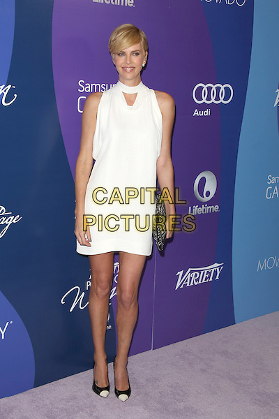 Charlize Theron<br /> at Variety's 5th Annual Power of Women event presented by Lifetime at the Beverly Wilshire Four Seasons Hotel in Beverly Hills, California, USA, October 4th 2013.<br /> full length white dress sleeveless cut out clutch bag black shoes toe cap two tone <br /> CAP/MPI/mpi25<br /> &copy;mpi25/MediaPunch/Capital Pictures