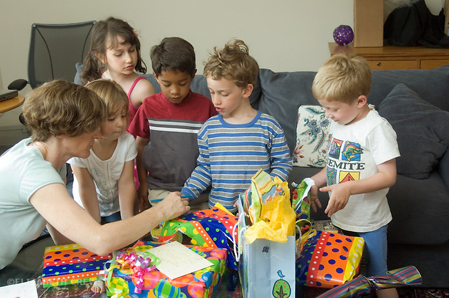 Berkeley CA  Mother helping four-year-old unwrap presents at his birthday party