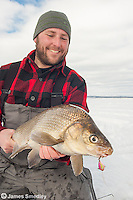 Angler holding a whitefish caught ice fishing in winter.