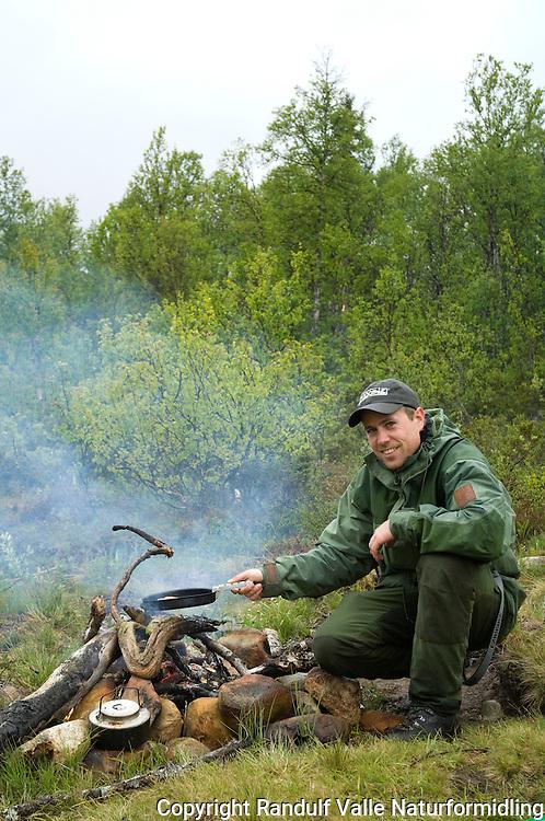 Mann ved lite bål i bjørkeskog ---- Man beside camp fire