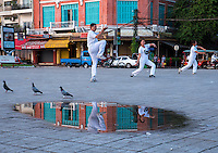 Reflection early morning of a group of people exercising, along the Boulevard and at the Bank of the Mekong River in Phnom Penh, Cambodia